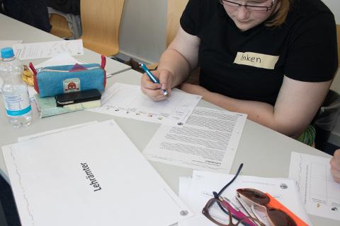 Eine Teilnehmerin füllt mit Hilfe von Informationsmaterial über einen Studiengang die Kreativzielmatrix aus