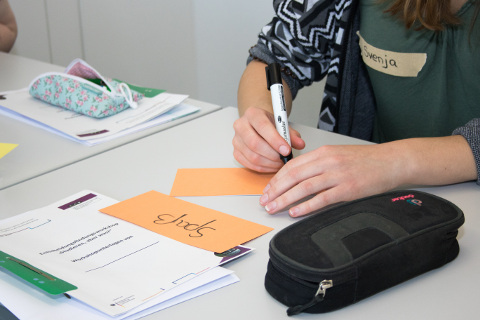 Eine Teilnehmerin hält ihren Beitrag auf einer Moderationskarte fest