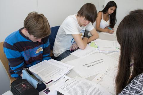 Mehrere Teilnehmerinnen und Teilnehmer informieren sich anhand von Informationsmaterial über Studiengänge der Mathematik und Naturwissenschaften